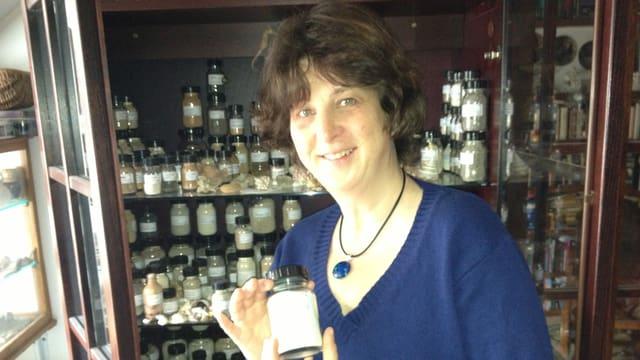 Veronika Geyer steht vor ihrem Schrank mit Fläschen, die mit Sand aus aller Herren Länder gefüllt sind.