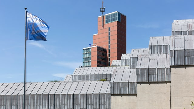 Das Theater Winterthur, dahinter ein roter Turm, davor weht eine blaue Fahne