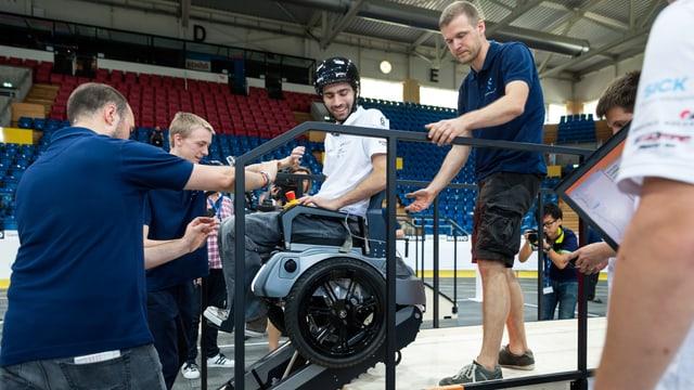 Ein Mann in einmem Rollstuhl mit Raupenantrieb überwindet als Hindernis eine Treppe.