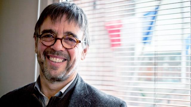 Ein lachender Mann mit Brille.
