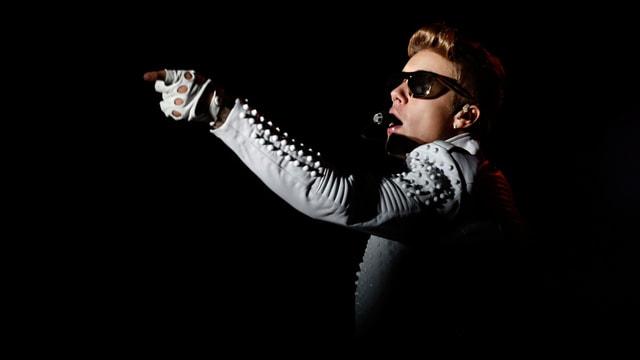 Ein junger Mann vmit Sonnenbrille streckt seinen Arm aus und singt vor schwarzem Hintergrund.