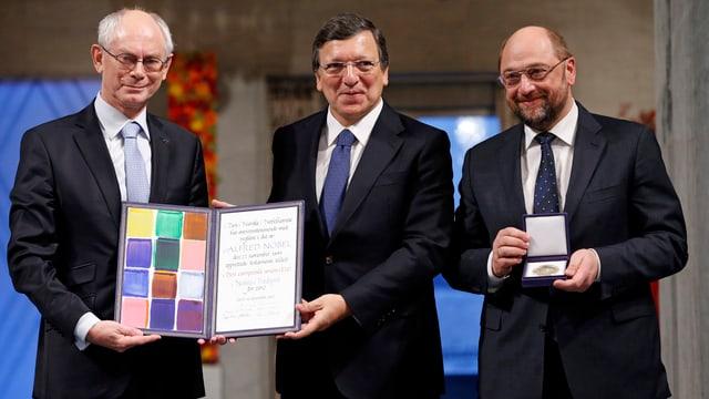 Die drei Männer mit einer Urkunde und einer Medaille in den Händen.