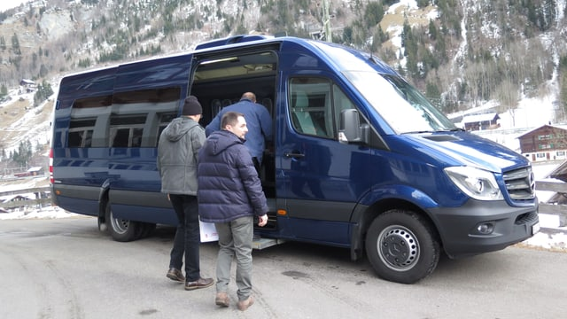 Ein blauer Minibus, in den Leute einsteigen.