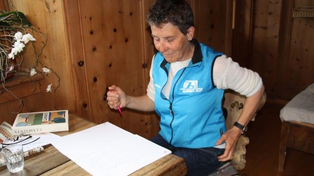 Eine Frau mit weissem Shirt und hellblauer Weste sitzt vor einem aufgeschlagenen Heft an einem Tisch.
