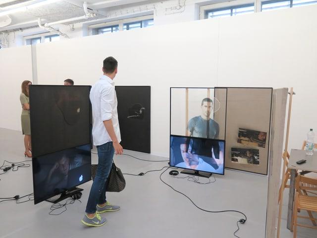 Ein Mann läuft durch einen Raum mit Bildschirmen und Glasscheiben.