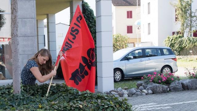 Eine Frau steckt eine Flagge der Juso in die Erde.