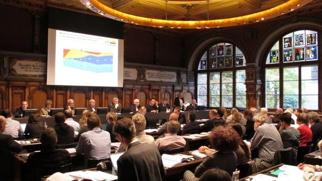Holzgetäferter Ratssaal mit Parlamentariern und Projektionswand