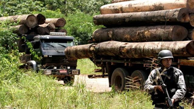 Soldat mit Gewehr vor Holztransportern