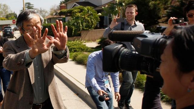 Ein 65-jähriger Japaner, umringt von Kameraleuten und Journalisten, hält schützend seine Hände vors Gesicht.