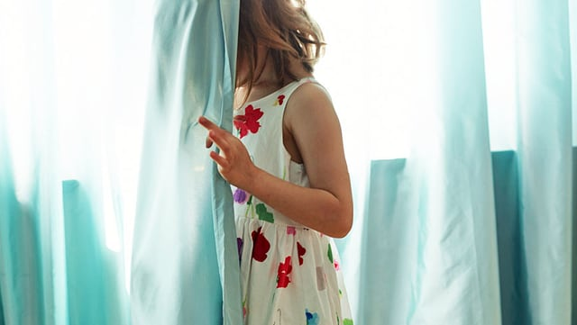 Ein Mädchen im Sommerkleid versteckt sich hinter einem hellblauen Vorhang.
