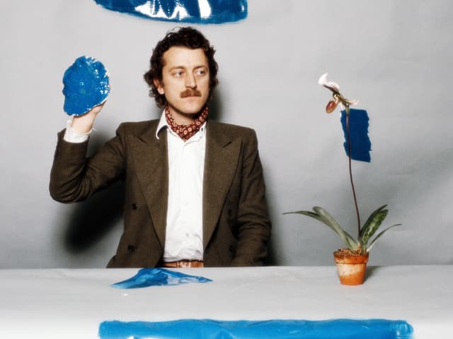 """Dieter Meier sitzt an einem Tisch, auf der eine Pflanze steht. Auf dem Tisch und an der Wand sind längliche Farbflecken zu erkennen, in seiner Hand hält er ebenfalls einen """"Farbklecks""""."""