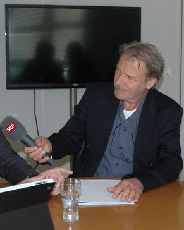 Reinhard Eyer sitzt am Tisch mit einem SRF-Mikrofon.