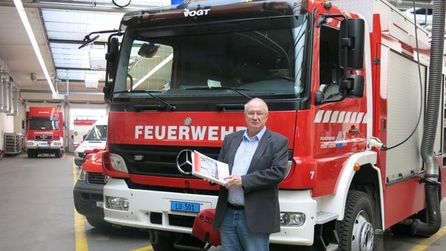 Peter Frey steht vor einem Feuerwehrauto in der Fahrzeughalle der Feuerwehr der Stadt Luzern.