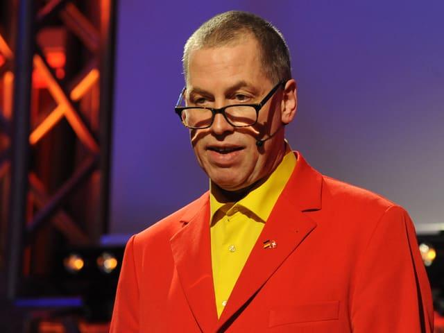 Thomas C. Breuer in seinem roten Anzug.