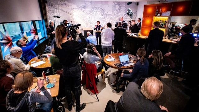 Cussegliera federala Doris Leuthard circumdada da schurnalistas e schurnalists en in'ustaria a Berna.