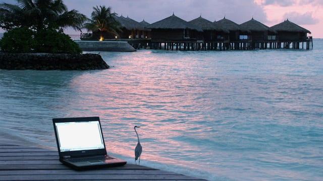 Ein Steg, darauf ein Laptop, im Hintergrund Häuser auf Stelzen.
