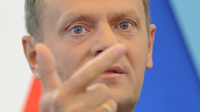 Porträt Tusk, seine Hand im Vordergrund.