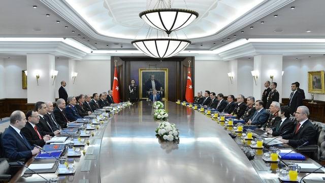 Kabinettsmitglieder sitzen an einem ovalen Tisch.