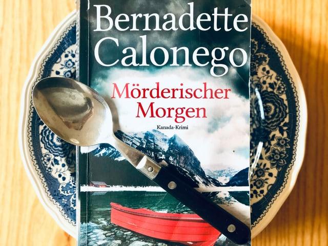Der Krimi «Mörderischer Morgen» liegt auf einem blau gemusterten Suppenteller. Ein Esslöffel ist über das Buch gelegt.