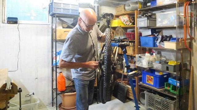 Ein Mann steht in einem Keller und schraubt an seinem Mountainbike.
