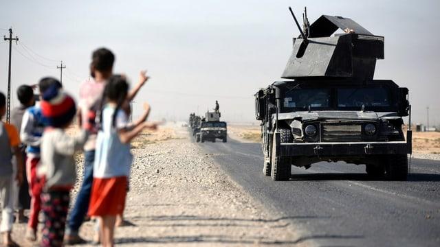 Eine Kolonne gepanzerter Fahrzeuge, am Strassenrand winken Kinder den Soldaten zu.