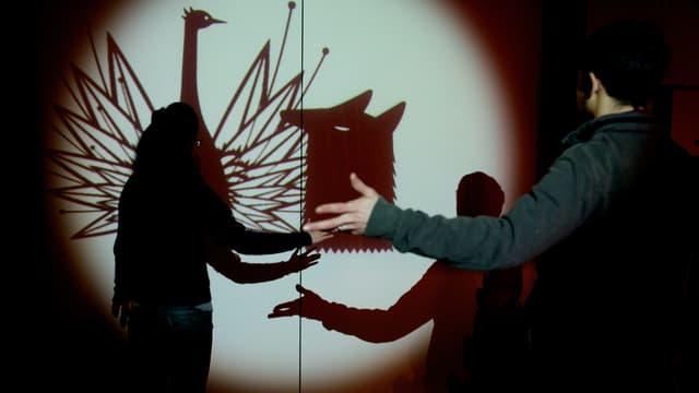 Zwei Menschen werfen ihre eigenen Schatten auf die Schattenprojektion mit Scherenschnitten eines Vogels und eines Wolfes.