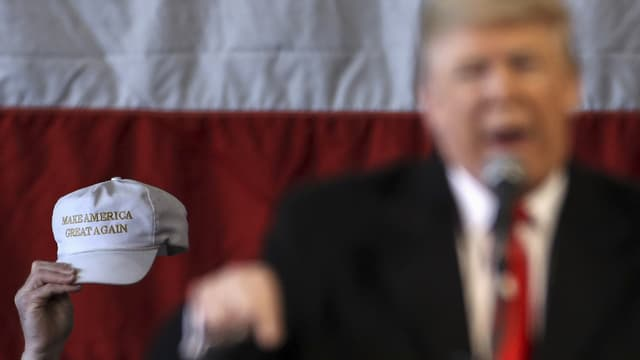 Auf einer Kappe steht «Make America great again», daneben ist unscharf Trump zu erkennen.
