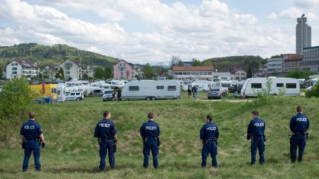 Polizisten vor Wohnwagen.