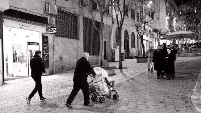 Ein älterer Mann schiebt einen Kinderwagen mit Säcken voller Flaschen durch die Fussgängerzone in Jerusalem
