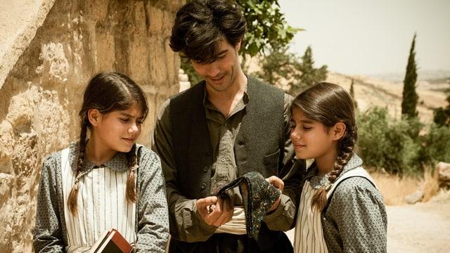 Ein Mann zeigt zwei Mädchen einen Schal.