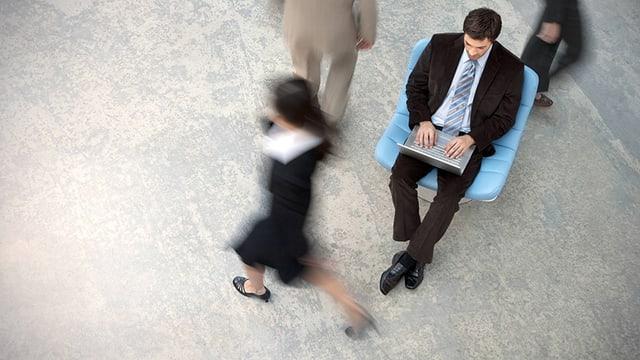 Vogelperspektive: Ein Geschäftsmann sitzt auf einem Stuhl, ein Laptop auf dem Schoss. Um ihn herum gehen drei Leute vorbei.