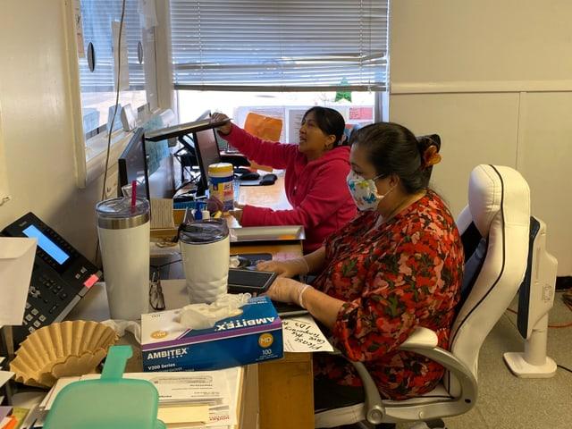 Zwei Frauen mit Masken an einem Schreibtisch.