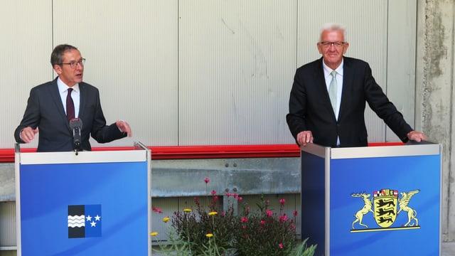 Zwei Männer hinter zwei Redepulten
