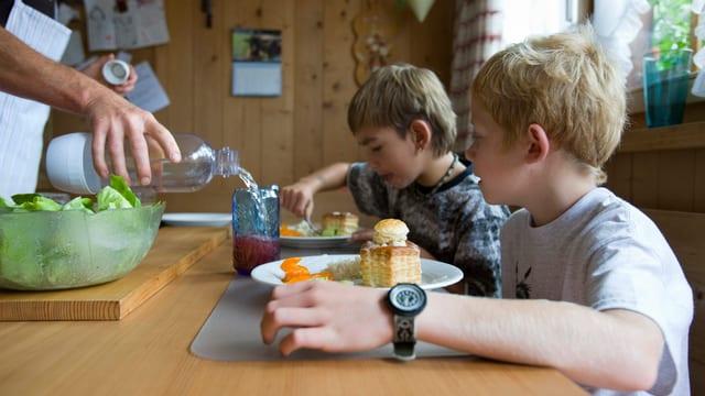 Zwei Kinder sitzen an einem Tisch und essen Pasteli.