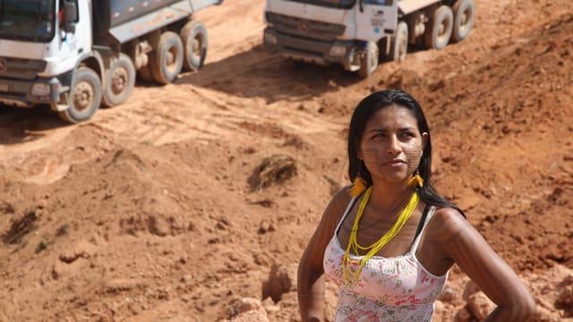 Eine dunkelhäutige Frau im Trägershirt steht mit angewinkelten Armen in einer Goldmine.