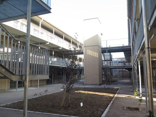Blick in das Innere der neuen Siedlung Fogo. In der Mitte braune Erde, darum herum ein Holzbau mit Balkonen.