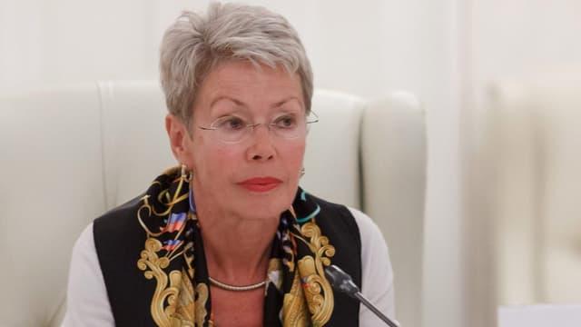 Botschafterin Heidi Tagliavini mit Foulard auf einem weissen Sessel am Mikrofon.