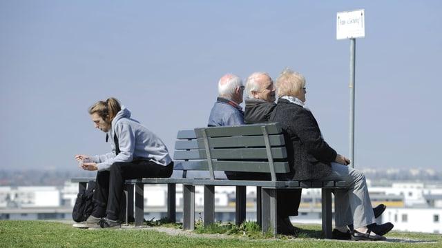 Symbolbild: Rentner sitzen auf einer Bank, auf der anderen Seite ein rund 30-jähriger Mann.