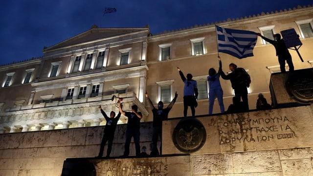 Menschen vor dem griechischen Parlament mit Griechen-Flagge.