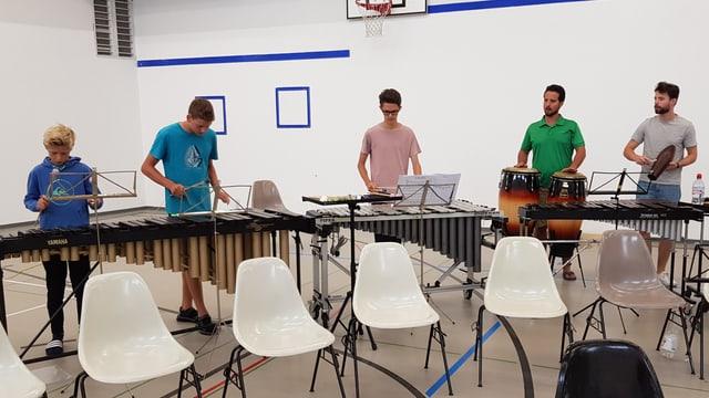 Plirs musicists vid instruments da percussiun.