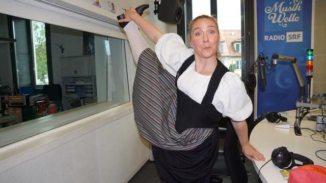 Eine junge Trachtenfrauen zieht mit ihrer rechten Hand ihr rechtes Bein senkrecht in die Höhe.