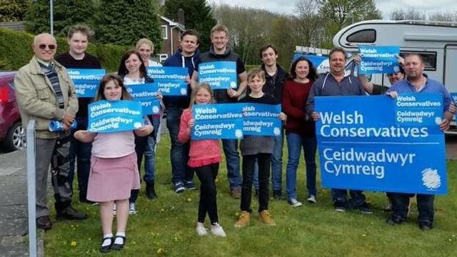 Frauen, Männer und Kinder tragen blaue Transparente mit der Aufschrift «Welsh Conservatives».