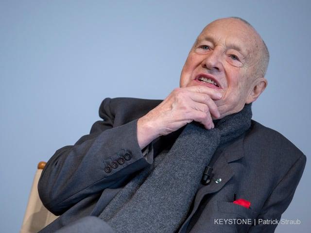 Georg Baselitz sitzt in einem Sessel und fasst sich ans Kinn.