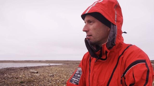 Ein Mann steht an einem steinigen Strand, er hat eine rote Wetterschutzjacke an.