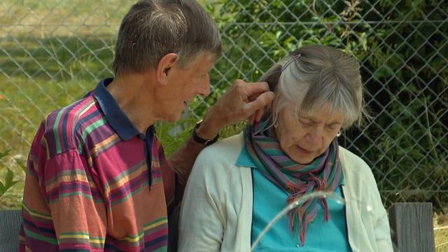 Senioren-Ehepaar, Mann streicht die Haare seiner Frau zurück.