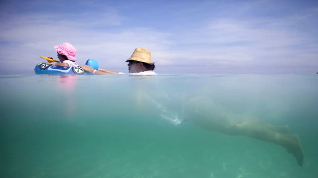 Frau mit Hut schwimmt im Meer und schiebt ein Baby im Schwimmring vor sich her.