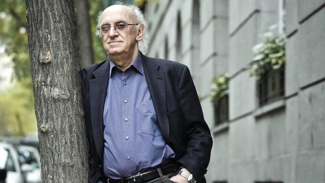 Der griechische Autor Petros Markaris lehnt an einen Baum.