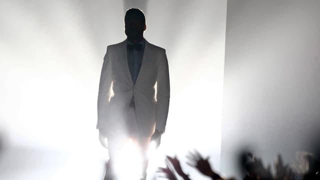 Ein Mann in weissem Anzug schreitet durch grelles Licht, unter ihm versuchen Hände nach ihm zu greifen.