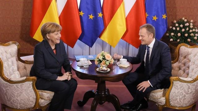 Merkel und Tusk sitzen an einem Tisch.