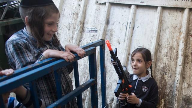 Zwei Kinder spielen, ein Mädchen hält eine Plastikwaffe in der Hand.